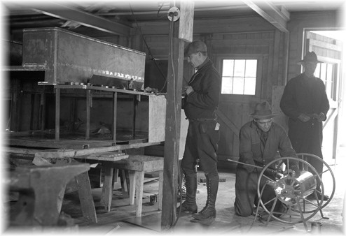 1938-The  Rangers and CCC's  building a pumping unit for a forest ranger truck at the Saranac Inn Ranger Barracks and Shop.
